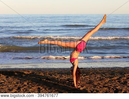 Young Athlete With Legs Turned Upwards Makes Pirouettes On The Sea Beach