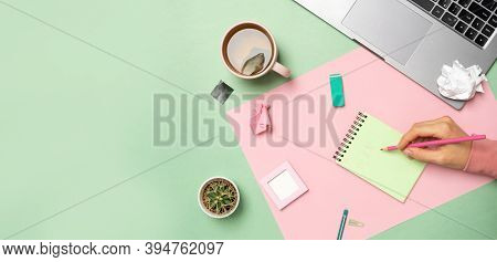 Pastel Office Table With A Laptop, Notepad, And A Womans Hand Is Writing. Top View With Copy Space,