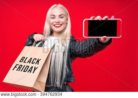 Happy Woman Consumer In Black Dress With Shopping Bags Isolated On A Red Background. Woman With Smar