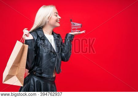 Happy Woman Consumer In Black Dress With Shopping Bags And Cart For Shopping Isolated On A Red Backg