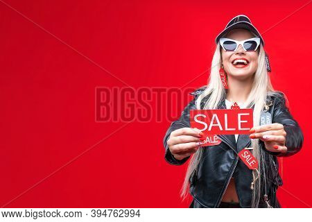 Beautiful Blonde Girl With Red Price Tags Hang On Stylish Leather Clothes. Young Bright Woman In Sun