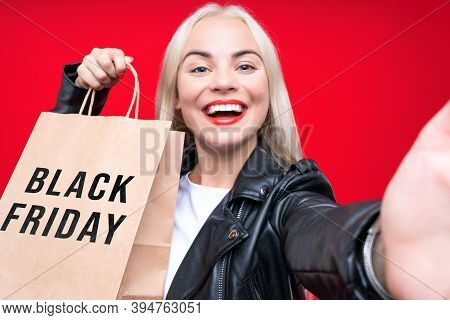 Close Up Of Happy Woman Consumer In Black Dress With Shopping Bags Isolated On A Red Background. Sho