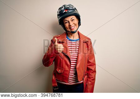 Middle age motorcyclist woman wearing motorcycle helmet and jacket over white background doing happy thumbs up gesture with hand. Approving expression looking at the camera showing success.