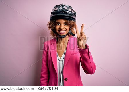 African american motorcyclist woman with curly hair wearing moto helmet over pink background showing and pointing up with fingers number two while smiling confident and happy.