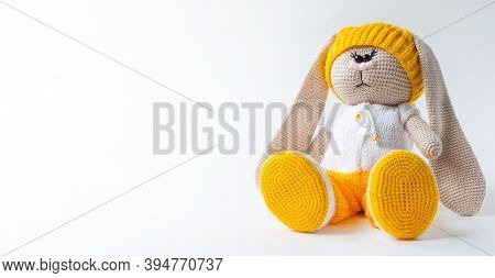 Kids Toy Plush Hare Sitting On A White Background. Soft Toy Is Child Protection Symbol