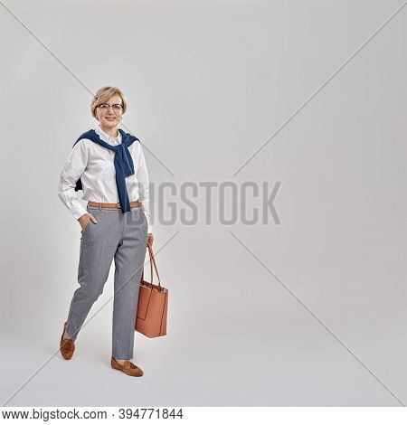 Full Length Shot Of Elegant Middle Aged Caucasian Woman Wearing Business Attire And Glasses Smiling