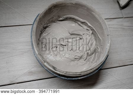 Putty Cement In Bucket On Floor For Rebuild Wall At Home - Can Use To Display Or Montage On Product.