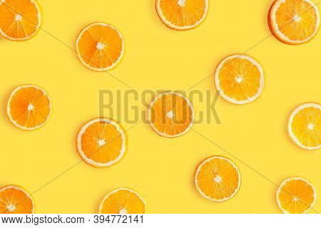 Top View Of Pattern, Laid Out Slices Of Juicy Oranges On Yellow Background. Summer Tropical Citrus F