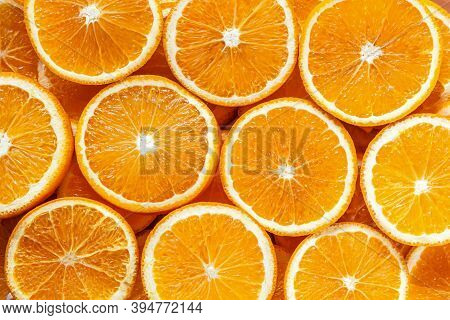 Closeup Top View Of Pattern, Laid Out Slices Of Juicy Oranges On Background. Summer Tropical Citrus