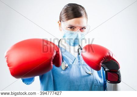 Young Female Caucasian Doctor Wearing Blue Uniform And Red Boxing Gloves, Professional And Confident