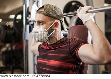 Young Caucasian Man Lifting Weights In Us Gym Wearing Protective Rubber Latex Gloves & Face Mask,cov