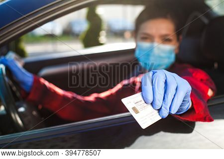 Young Female Driver Showing Coronavirus Health Card Or Immunity Passport,proof That A Person Has Dev