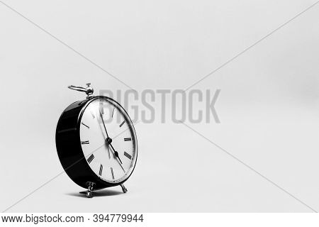 A Wide Portrait Of A Small Old Fashioned Antique Alarm Clock With Roman Numbers On The Dial On An Or