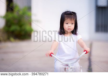 Asian Child Little Girl Is Riding A Bicycle On The Road. Children Ride A Tricycle Exercise Bike. Kid