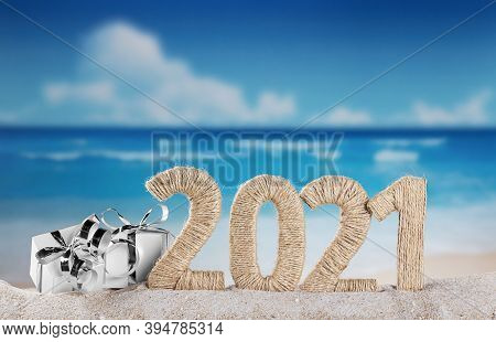 New Year 2021 On The Beach. Snowman And Christmas Gifts In The Sand