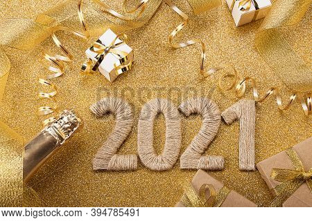 Happy New Year. Gold Background With 2021 Lettering, Craft Gifts, Champagne Bottle And Bright Christ