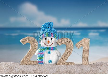 Concept Of The New Year In Hot Countries. Traditional Snowman In Sand In Inscription 2021 On Backgro