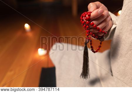 Close-up The Male Hand Of A Monk Practicing Meditation Holds A Red Rosary In A Dark Room By Candleli