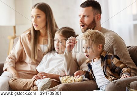 Astonished Parents And Kids Eating Popcorn And Watching Interesting Movie With Opened Mouths On Week