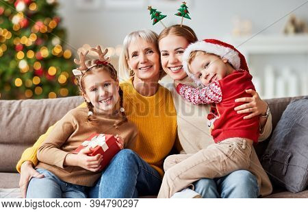 Happy Multi Generation Family Grandmother, Mother And Children Give Each Other Gifts, Hug And Smile