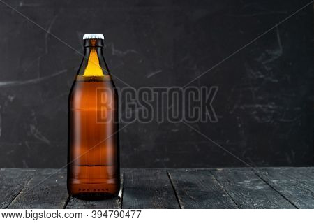 Closed Bottle Of Beer. Brown Bottle Of Beer. Amber Bottle On A Black Background.