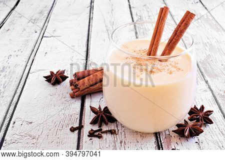 Spiced Christmas Eggnog Close Up On A Rustic White Wood Background
