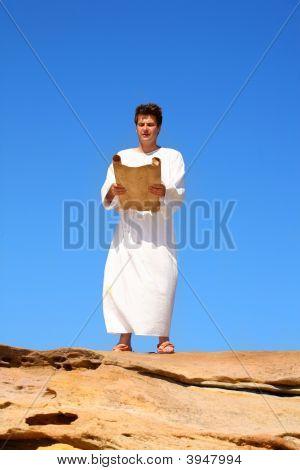 Man Reading Scroll In Rocky Desert Land Scape