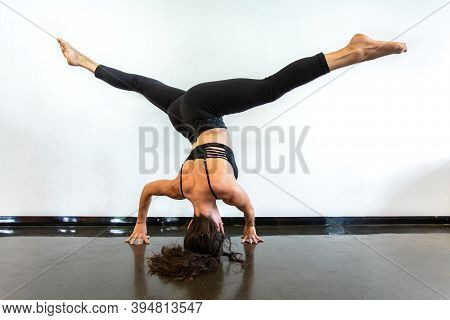 A Healthy And Toned Lady Is Seen From The Back As She Performs A Wide Legged Headstand Pose, Or Next