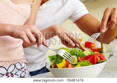 Close-up of human hands with forks mixing salad ingredients