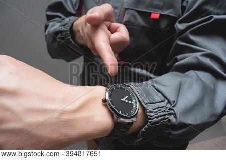 Car Service Worker Is Pointing On The Wrist Watch On His Hand Close Up. Fast Service.