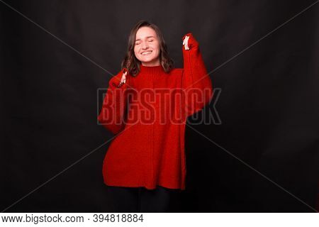Joyful Young Woman Is Smiling With Her Eyes Colsed And Is Dancing Near A Black Wall