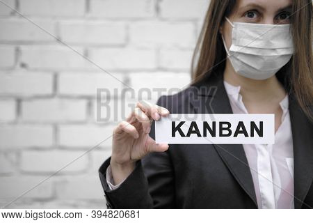 A European Girl Wearing A Medical Mask Holds A Sign With The Inscription Kanban, Against The Backdro