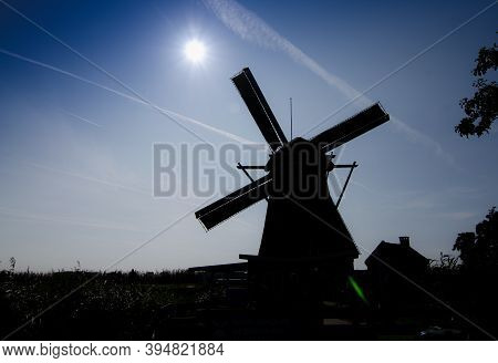 Kinderdijk, The Netherlands, August 2019. Conceptual Image At Sunset: The Silhouette Of The Mill Dom