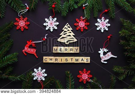 Christmas Festive Postcard With Christmas Tree Branches, Snowflakes, Christmas Toys And Wooden Lette