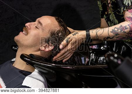 Minsk, Belarus - October 14, 2020: Tattooed Barber Washes Hair Of Visitor Gently And Carefully