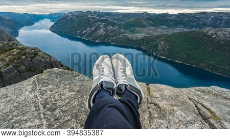 Man Resting At The Top Of Pulpit Rock With A Fjord At Preikestolen Under Beautiful Norway Landscape