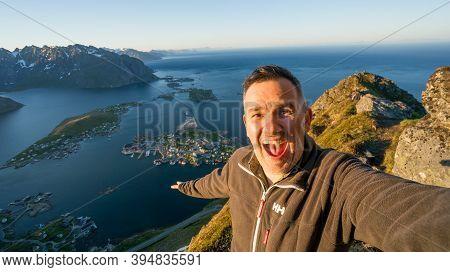 Reine, Norway - June 2016: Tourist Taking A Happy Selfie At Reinebringen, View On Stunning Mountains