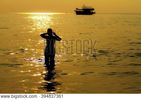 Sunset With Silhouette Woman And Boat On Beach At Koh Chang Thailand. Koh Chang Is Located In The Ea