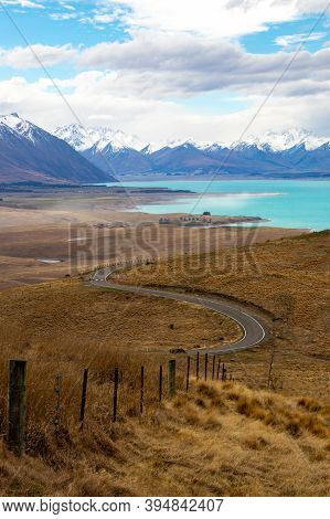 Nz Fence Runs Down To Road In Front Of Lake