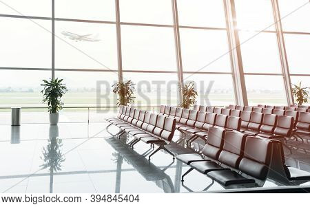 Empty Multiple Rows Of Seats In A Waitng Hall At The Airport Departure Terminal With An Airplane Tak