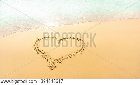 A Heart Shape Written On Golden Brown Sand Beach Beside Pastel Green Color Sea 's Water