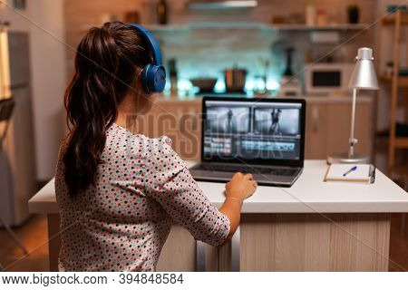 Video Editor Working On A Project From Home Kitchen During Night Time And Listening Music On Headpho