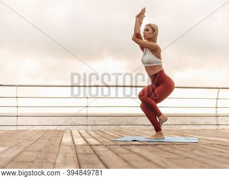 Yoga Practice At Sunrise. Young Woman Yogi Stands In Tree Pose On The Beach At The Morning