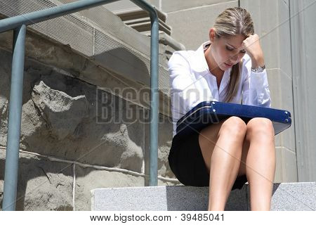A upset, depressed business woman sitting outside company