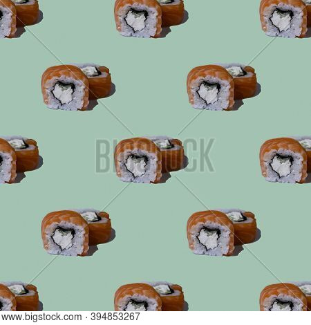 Food Pattern. Roll Philadelphia Sushi With Salmon On A Green Background. Seamless Pattern.