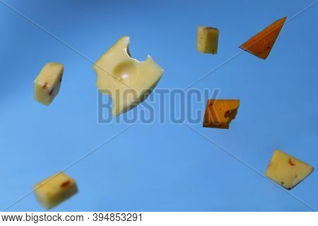 Levitation. Pieces Of Different Cheeses Are Floating In The Air. Pieces Of Different Cheeses On A Bl