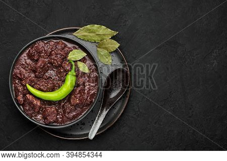 Dinuguan In Black Bowl On Dark Slate Table Top. Spicy Filipino Cuisine Pork Blood Stew Dish With Mea