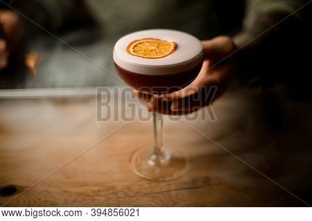 Mans Hand Holding Glass Of Drink With Foam At Smoky Bar Counter.