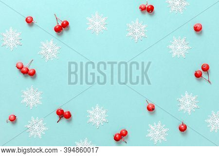 Holiday Christmas Background. White Snowflakes, Red Berry In Christmas Composition On Pastel Blue Ba