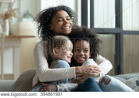 Overjoyed African American Woman Cuddling With Two Little Daughters